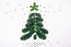 Winter flat lay style picture. Christmas tree made of fir branches. White wooden rustic background with little silver sparkles. Winter flat lay style picture Royalty Free Stock Photos