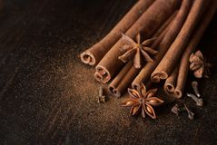 Winter flavors for drinks and cookies. Cinnamon sticks, carnation and anis close up on wooden table Stock Images