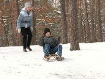 The winter flight. The boy slideing on sledge and the woman on snowy hill Royalty Free Stock Photos
