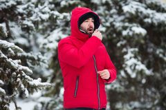 Winter flu concept. Male sneezing. Bearded man has flu and fever in winter day outdoor. Royalty Free Stock Photos