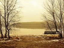 Winter fogy sunset over lake, cold orange sun rays between above water level. Melted first snow on the ground. Royalty Free Stock Image