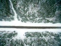 Winter forest and asphalt road. View from above. The photo was taken with a drone. Pine and spruce forest with a black road in the. Snow Stock Photo