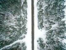Winter forest and asphalt road. View from above. The photo was taken with a drone. Pine and spruce forest with a black road in the. Snow Stock Photography