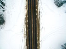 Winter forest and asphalt road. View from above. The photo was taken with a drone. Pine and spruce forest with a black road in the. Snow Stock Images