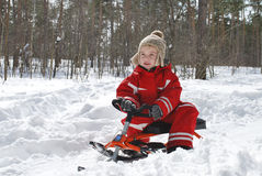 In winter, in the forest boy is sitting on a sled and smiling. Stock Image
