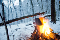 In the winter forest on fire boiled water in a pot. I Royalty Free Stock Image
