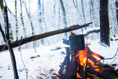 In the winter forest on fire boiled water in a pot. I Royalty Free Stock Photo
