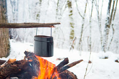In the winter forest on fire boiled water in a pot. I Stock Photo