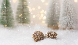 Winter forest with frosty fir trees falling snow pine cones golden garland bokeh lights. Christmas New Year greeting card poster. Banner. Magical festive stock photography
