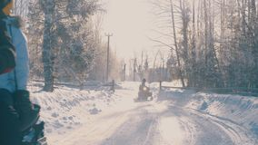 Winter forest in a hoarfrost. People on snowmobiles riding in the forest. stock footage