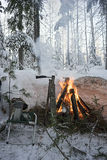 In the winter forest on a picnic at the burning fire. Stock Image