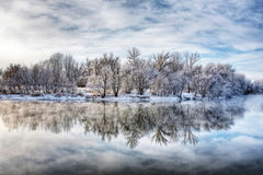 Winter forest river. With reflection of the sky Stock Photos