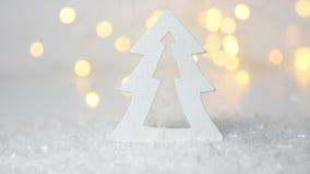 Winter forest scene. Christmas wooden decorative fir tree golden bokeh glittering lights falling snow. Creative footage New Year stock video