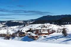 Winter forest scene. Small houses at the mountain in a sunny winter day. Snowy fairytale in Bulgaria. Winter forest scene. Small houses at the mountain in a Royalty Free Stock Images