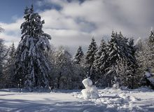 Winter forest with sitting snowman stock photo