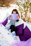 Winter, forest, sofa and woman reading book Royalty Free Stock Photos