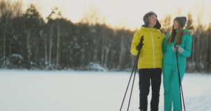 In the winter forest at sunset loving couple skiing and look around at the beauty of nature and attractions in slow stock video footage
