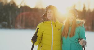 In the winter forest at sunset a man and a woman ski and look around at the beauty of nature and attractions in slow stock video footage