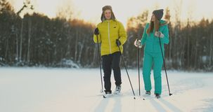 In the winter forest at sunset a man and a woman ski and look around at the beauty of nature and attractions in slow stock video