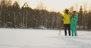 In the winter forest at sunset a man and a woman ski and look around at the beauty of nature and attractions in slow stock footage