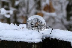 Winter forest through a transparent glass ball.  royalty free stock photography