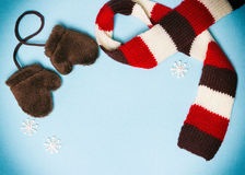 Winter frame with mittens, scarf and small snowflakes Royalty Free Stock Photo