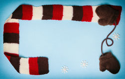 Winter frame with mittens, scarf and small snowflakes Stock Image