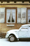 Winter in France. Impression of an old Citroen 2CV in front of a frame-work house in winter - Wissembourg - Alsace - France - grainy image, film scan Royalty Free Stock Photo