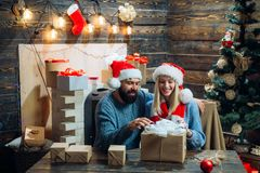 Winter freands wearing red santa claus hat. Hoppy couple over christmas tree lights background. Happy new year. Merry royalty free stock image