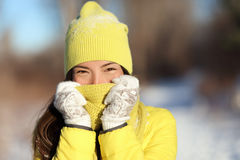 Winter freezing woman covering face from cold. Skincare concept. Cute Asian girl happy holding scarf with gloves over nose and mouth to protect from the frost stock photo