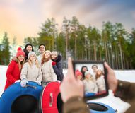Friends with snow tubes taking photo by tablet pc royalty free stock photography