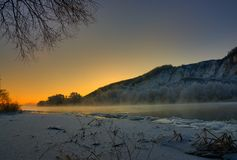Winter frosty morning before dawn. Freezing river. From the hilly banks and large ice floes Royalty Free Stock Photos