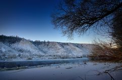Winter frosty morning before dawn. Freezing river from the hilly. Banks and large ice floes Royalty Free Stock Photo