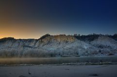 Winter frosty morning before dawn. Freezing river. From the hilly banks and large ice floes Royalty Free Stock Photography