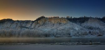 Winter frosty morning before dawn. Freezing river. From the hilly banks and large ice floes Stock Photography