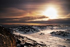 Winter frosty night landscape the Arctic Ocean. Northern severe cold nature cliffs yellow moon light and clouds, black. Rocky coast. The Barents Sea, Kola stock image