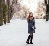 Winter full length portrait of a cute redhead lady in grey coat and scarf posing in the park Stock Image