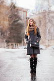 Winter full length portrait of a cute redhead lady in grey coat and scarf posing on the street Stock Image