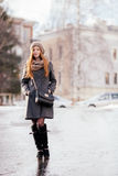 Winter full length portrait of a cute redhead lady in grey coat and scarf posing on the street Stock Photos