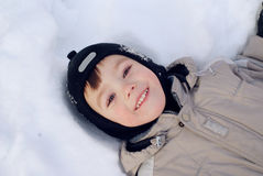 Winter fun. Little boy is lying on the snow and smiling Royalty Free Stock Photos