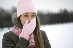 Winter fun. Girl in the Park laughs, closes his hand in mittened pink Stock Image
