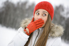 Winter fun. Girl in the Park laughs, closes his hand in mittened red Royalty Free Stock Photos