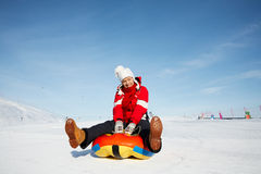 Winter fun. Caucasian woman is sliding fast downhill on an inner tube Stock Image