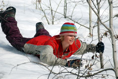 Winter fun. A girl slides down a snow-covered slope, belly-down enjoying the winter weather royalty free stock image
