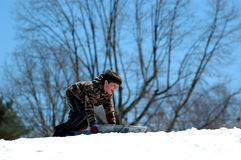 Winter fun. A boy at the top of a snow covered hill with a sled full of excitement Stock Images