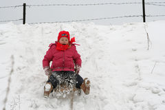 Winter fun. A little girl sliding Royalty Free Stock Photo