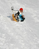 Winter fun. Mother and son sliding down from hill Royalty Free Stock Photo