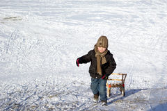 Winter fun. Boy with the sledge on suny winter day Stock Images