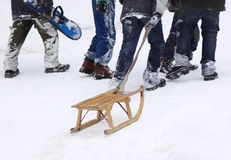 Winter fun. Boys climbing up the snowy hill with sledge and snowboard, focus on sledge Stock Photos