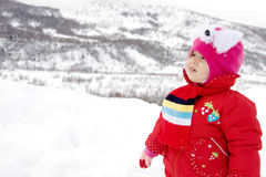 Winter fun. Toddler girl dressed in red having fun in the snow Royalty Free Stock Images